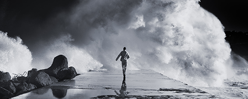 man running next to giant wave